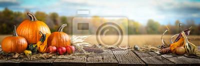 Image Action de grâce avec des pommes potirons et des épis de maïs sur une table en bois avec arbres de champ et ciel en arrière-plan