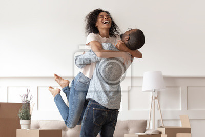 Image African husband lifting happy wife celebrating moving day with boxes