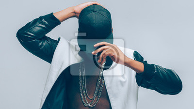 Image Afro american urban guy. Rapper posing in cap and leather jacket on naked torso. Head tilted down. Rap culture lifestyle.
