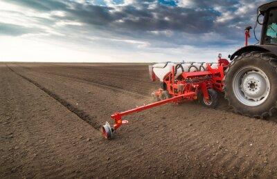 Image Agriculteur avec semoir de tracteur - semer des cultures au champ agricole au printemps