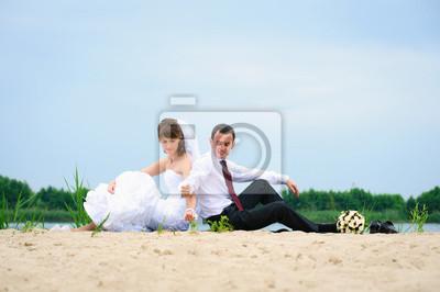 aimer couple de jeunes mariés assis près de l'eau et des sables répandent