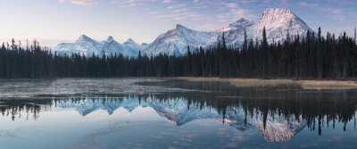 Image Almost nearly perfect reflection of the Rocky mountains in the Bow River. Near Canmore, Alberta Canada. Winter season is coming. Bear country. Beautiful landscape background concept.