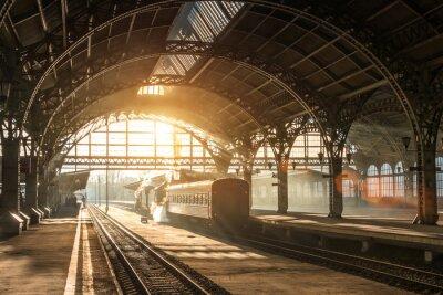 Image Ancienne gare avec un train et une locomotive sur le quai en attente de départ. Les rayons du soleil du soir dans les arcs de fumée.