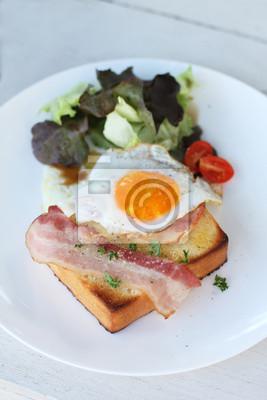 Assiette de petit déjeuner avec œuf au plat, bacon et des toasts