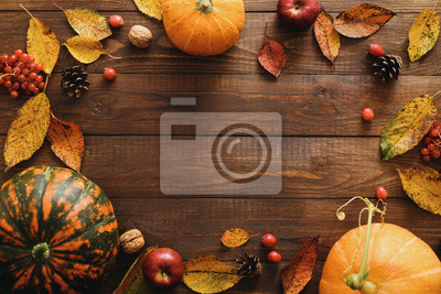 Image Autumn frame made of pumpkins, dried fall leaves, apples, red berries, walnuts, pine cones on wooden table. Thanksgiving, Halloween, Autumn Harvest concept. Flat lay composition, top view, copy space