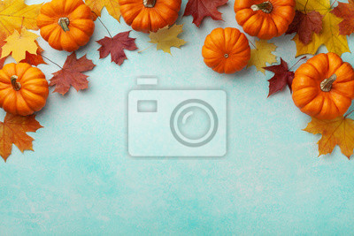 Image Autumn Thanksgiving background. Pumpkins and maple leaves on turquoise table top view.