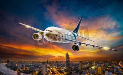 Image Avion de transport survolant la ville de la scène de nuit sur fond de coucher de soleil magnifique