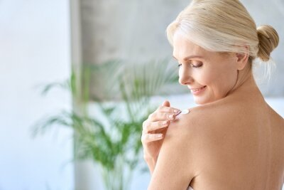 Image Back view of naked gorgeous middle aged 50s woman applying moisturizing body lotion after shower. Advertising of bodycare spa procedures, antiage sun protection treatment products concept.