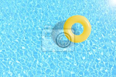 Image Bague de piscine jaune flottante en eau bleue. Concept couleur été.