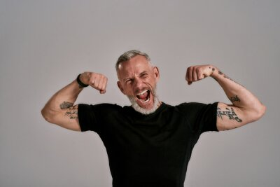 Image Be more, do more. Angry middle aged muscular man in black t shirt shouting at camera, showing his biceps while posing in studio over grey background