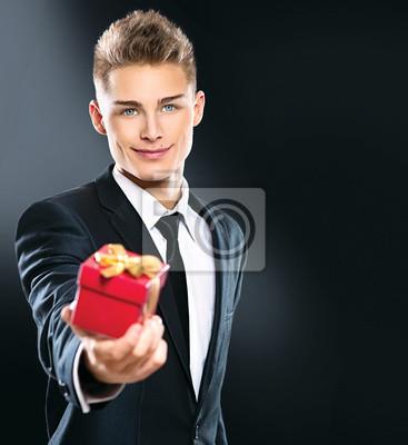 Beau Jeune Homme beau jeune homme donnant boîte-cadeau rouge. daffaires élégante