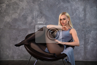 Image Beautiful blonde girl in pantyhose posing in the chair.