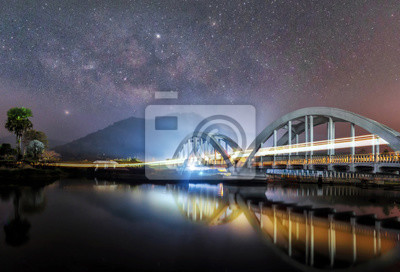 Beautiful Light from the train that runs through the Tha Chom Phu white bridge over the river at night in the sky among the stars and the Milky Way.The bridge has a reflecting in the water