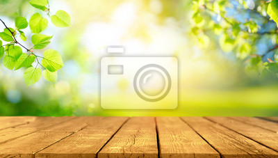 Image Beautiful spring background with green juicy young foliage and empty wooden table in nature outdoor. Natural template with Beauty bokeh and sunlight.