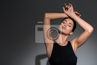 Image beautiful young model posing with closed eyes on black background with copy space