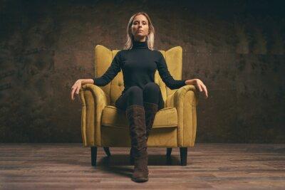 Image Beautiful young stylish woman in black wear sitting in yellow armchair.