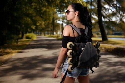 Image Belle brune fille avec sac à dos derrière le dos dans quels patins à roulettes
