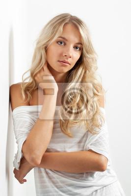 belle femme blonde près du mur blanc