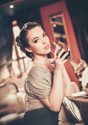 Image Belle jeune fille avec un verre de rouge winein un restaurant