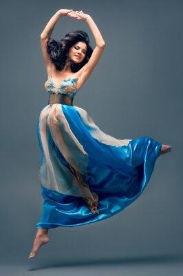 Image belle jeune fille flottant dans, robe de soie bleue mi-air