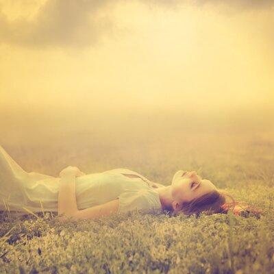 Image Belle jeune fille rêve de mentir sur une prairie au printemps magique