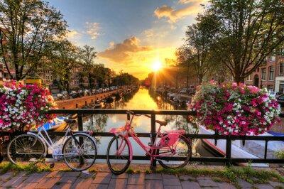 Image Belle lever de soleil sur Amsterdam, Pays-Bas, avec des fleurs et des vélos sur le pont au printemps