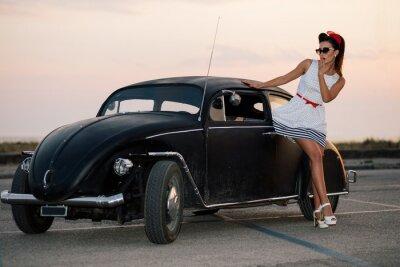 Image Belle pin-up girl posing avec la voiture de route chaude