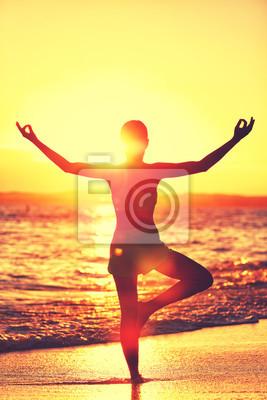 Bien-être de l'esprit - Yoga femme debout sur une jambe faisant arbre pose avec les bras ouverts ouverts dans le coucher du soleil flare faire matin routine d'exercice sur la plage tropicale. Mindfuln
