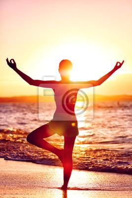 Bien-être de l'esprit - Yoga femme debout sur une jambe faisant arbre posent avec les bras ouverts ouverts dans le flare du coucher du soleil en face de l'océan sur la plage. Mindfulness et concept de
