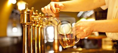 Bière d'or dans la main et robinets de bière