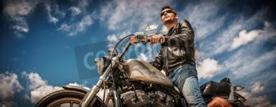 Image Biker homme portant une veste en cuir et des lunettes de soleil assis sur sa moto.