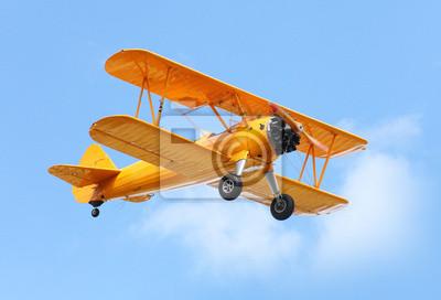 Image Biplan jaune sur le ciel bleu.