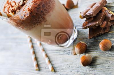 Boisson chocolatée dans le verre sur fond de bois avec des noix