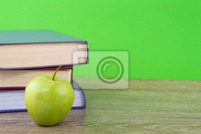 books with apple on a green background