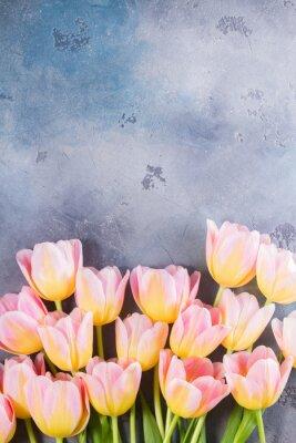 Image Bordure de tulipes roses et jaunes sur fond de pierre grise avec copie espace