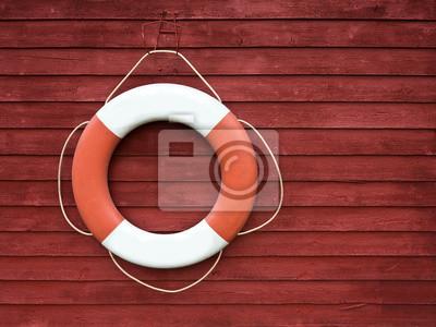 Bouée de sauvetage rouge et blanc accroché sur le côté d'un bateau en bois