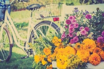 Image Bouquet de fleurs sur une chaise blanche. Vélo rétro brouillé dans l'arrière-plan.