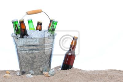 Bouteilles de bière assortis dans un seau de glace dans le sable