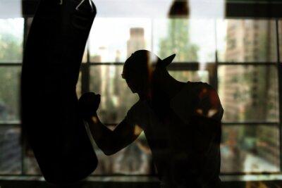 Image Boxer frappe un sac de boxe contre la fenêtre, séance d'entraînement