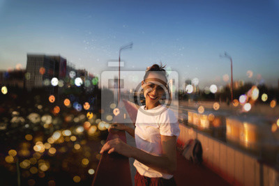 Image Bright summer lifestyle portrait of young pretty woman in eyewear, red skirt and white T-shirt, standing on the bright red bridge at evening with city background and blurred bokeh.
