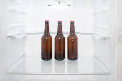 Image Brown glass beer bottles stand on a shelf in the refrigerator