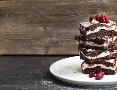 Image Brownies-cheesecake tower with raspberries on white plate
