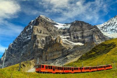 Image Célèbre train touristique rouge électrique descendant de la station du Jungfraujoch (en haut de l'Europe) à Kleine Scheidegg, Oberland bernois, Suisse, Europe