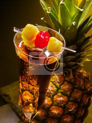 Champagne cocktail avec décoration de cerise et ananas entier avec des feuilles.