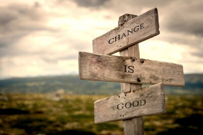 Image Change is good quote on wooden signpost in nature with moody background. Motivational, move on, changes, choice, choices concept.