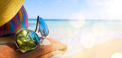 Image Chapeau de paille, sac et des lunettes de soleil sur une plage tropicale