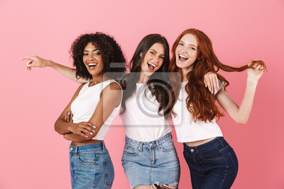 Image Cheery young three multiethnic girls friends posing isolated over pink wall background.