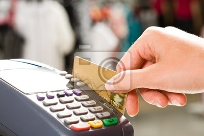 Close-up de la main tenant une carte en plastique dans la machine de paiement