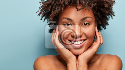 Image Close up portrait of relaxed black woman has gentle skin after taking shower, satisfied with new lotion, has no makeup, smiles tenderly, shows perfect teeth, stands shirtless against blue background