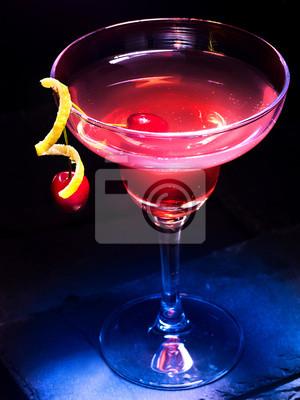 Cocktail d'alcool à la grenade avec décoration de citron et de cerise. Cocktail d'alcool sur fond noir.